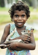 Tamisa Pootchemunka, three, cuddles a baby wallaby found wandering the township of Aurukun outside her home.
