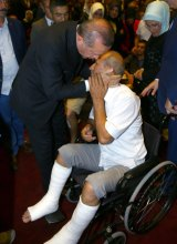 Mr Erdogan hugs a wounded civilian during the commemorative event in Ankara.