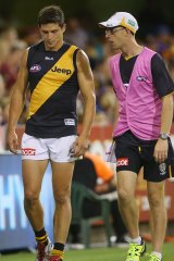 Richmond's Chris Knights leaves the field injured during the match against the Brisbane Lions.