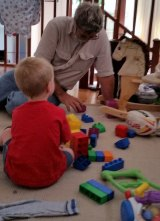 Mike playing with his grandson; he would do it for love, but appreciates the money the Registered Care Provider scheme brings in.