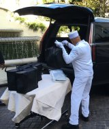 A Peninsula Hotel bellboy loads picnic hampers into the Cadillac.