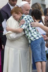 Pope Francis hugs eight-year old Simone Zanini at the Vatican earlier this month.