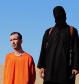 An Islamic State executioner stands beside British aid worker David Haines before he was beheaded.