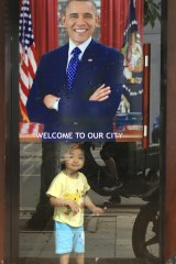 A young girl smiles under a poster of US President Barack Obama in Hanoi, Vietnam.