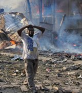 A man walks past destroyed buildings at the scene of a blast in Mogadishu, Somalia.