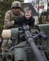 A member of the US Army's 2nd Cavalry Regiment shows a gun to a young boy on a Stryker vehicle during the ''Dragoon Ride'' in Salociai.