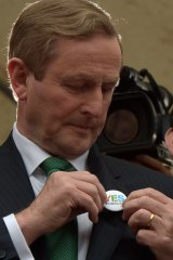 Irish Prime Minister Enda Kenny puts on a Yes vote campaign badge.