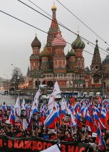 Russians carrying protest banners march in memory of assassinated opposition leader Boris Nemtsov.