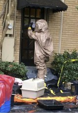 A man wearing a hazardous material suit prepares to remove a pet dog, named Bentley, from the home of a nurse infected with Ebola.