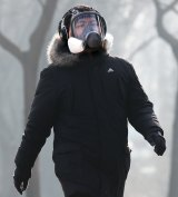 A man wearing a mask for protection against pollution exercise at Ritan Park during a heavily polluted day in Beijing.