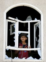 A boy looks through a window of his home damaged by an air strike near Sanaa Airport.