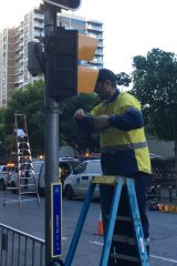 A worker installs yellow coverings to make Brisbane pedestrian lights look like those in New York for the Thor:Ragnarok filming.