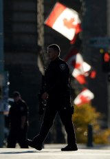 A country shaken: Police continue to patrol a street near the National War Memorial in Ottawa, Ontario.