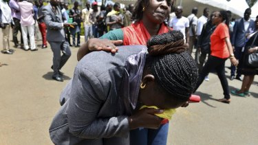 Grief: A relative is assisted by Red Cross staff as bodies of the students killed in the attack arrive at Chiromo Mortuary in Nairobi.