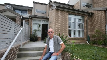A $70,000 dilemma: John Barnes on the steps of a town house he purchased off the plan in Berowra Heights.