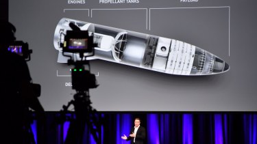 Elon Musk, and behind him a design for space transport, is seen during a presentation at the International Astronautical Congress in Adelaide.