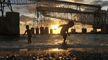 Children play beneath the hulking cantilevers used to load phosphate on ships.