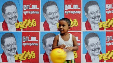 A Sri Lankan boy in Colombo stands next to a wall of election campaign posters spruiking Sri Lankan President Mahinda Rajapaksa.