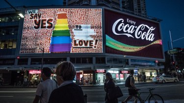 The Coca-Cola sign in Sydney's Kings Cross lights up in rainbow colours.