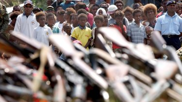 The international mission collects firearms under an amnesty in 2003 as Solomon Islanders watch on.