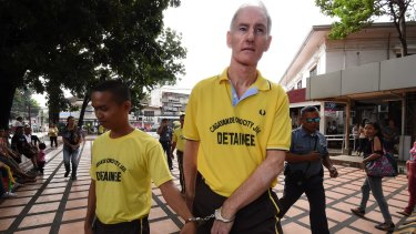 Peter Scully (right) arrives at the Cagayan De Oro court handcuffed to another inmate on the first day of his trial.