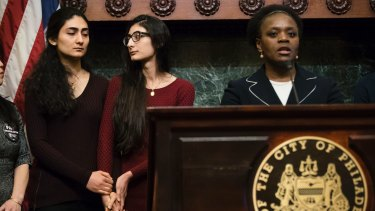 Farzaneh Ahmadi Darani, left, and her sister Shadi Ahmadi Darani hold each others' hands during a news conference in Philadelphia. Attorney Ayodele Gansallo speaks.