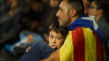 A man and his child listen to a televised speech by Mariano Rajoy, Spain's Prime Minister.