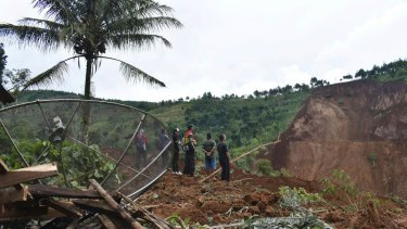 Rescuers search for victims in a neighborhood hit by a landslide in the village of Banaran, Ponorogo, East Java, Indonesia.