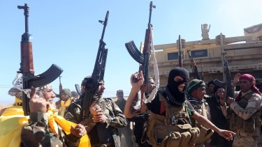 Iraqi pro-government fighters celebrate as they advance into Tikrit.