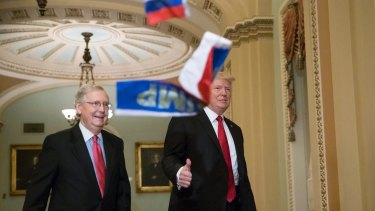 """Small Russian flags bearing the word """"Trump"""" are thrown by a protester towards President Donald Trump, as he walks with Senate Majority Leader Mitch McConnell, on Wednesday."""