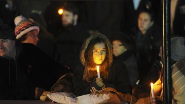 A girl holds a candle at the Anzac Day dawn service.