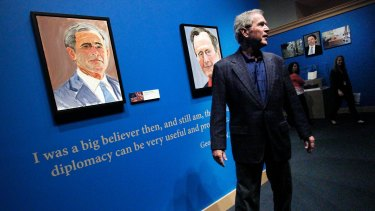 George W. Bush tours an exhibit of his paintings at his library in 2014.