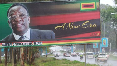 Traffic flows past a billboard with a portrait of Emmerson Mnangagwa.