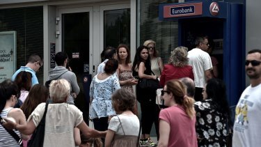 People queue at a national Bank of Greece ATM in central Athens.