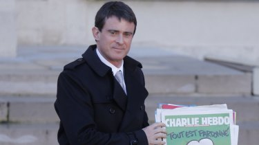 """French Prime Minister Manuel Valls holds a copy of <i>Charlie Hebdo</i> with the title """"Tout est pardonne"""" (""""All is forgiven"""") as he leaves the weekly cabinet meeting at the Elysee Palace in Paris."""