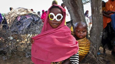 A young Somali girl displaced by drought wears mock spectacles cut from an antibiotics medicine box at a relief camp near the capital, Mogadishu, in March 2017.