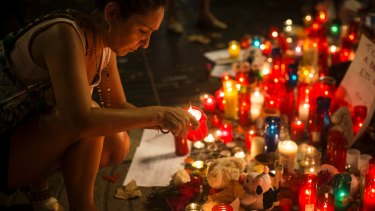A woman lights up a candle at a memorial tribute to the victims of the vehicle attacks on Barcelona's historic Las Ramblas promenade.