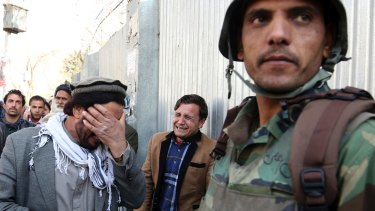 Men cry after an attack on a military hospital in Kabul, Afghanistan.
