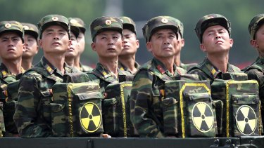 North Korean soldiers look towards their leader Kim Jong-un during a military parade, carrying packs marked with the nuclear symbol.