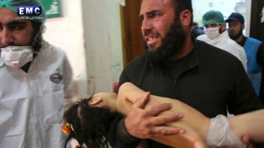 A man carries a child following the suspected chemical attack in the town of Khan Sheikhoun.