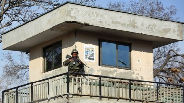 An Afghan soldier stands guard at the military hospital after the attack.