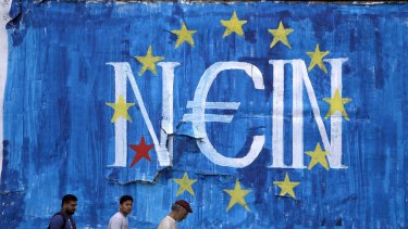 "Men walk by an anti-EU graffiti in Athens, Greece. The word painted in German over the European Union flag reads, ""No""."