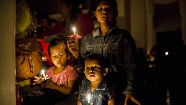 Christian worshipers hold candles as they attend a mass in Aceh, Indonesia.