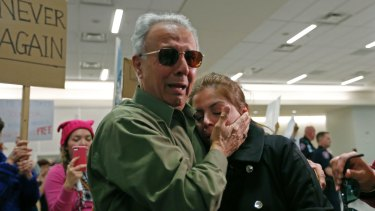 Iranian green card holder Shima Behgooy, right, cries on the shoulders of her father-in-law Ahmad Behgooy, a native of Iran who is now a US citizen, after she was released at Dallas-Fort Worth International Airport.