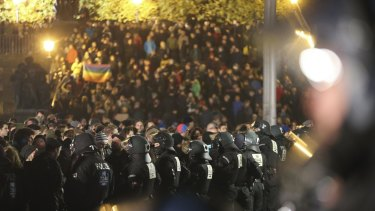 German police officers stand in a line in front of protesters against a demonstration marking the first anniversary of Pegida in Dresden on Monday.