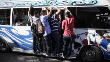 Riding on a  mini bus during the suspension of public transport services in San Salvador on Monday.