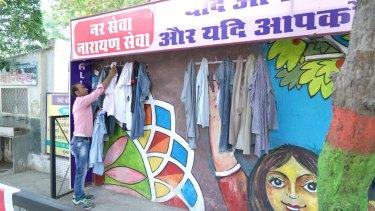 A man inspects a shirt at the wall in Bhilwara.