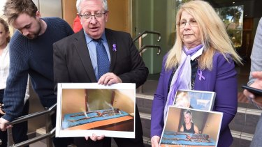 Mark and Faye Leveson hold photos of the skeletal remains of their son Matthew Leveson after giving their impact statement at the Coroner's Court  on Friday.