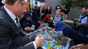 """""""Who's winning?"""": children at the centre play Snakes and Ladders."""