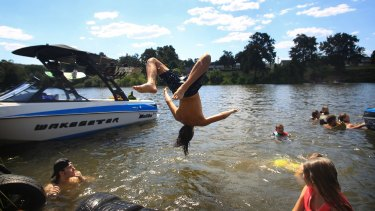 Children hit the Nepean River at Penrith to get some relief from the heat.